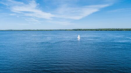 A small sailing riverboat of white color sailing along the sandy riverbank overgrown with green grass. View from above. Stock Photo