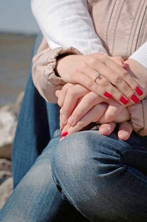 loving hands: Loving couple holding hands with weddind ring and red nails