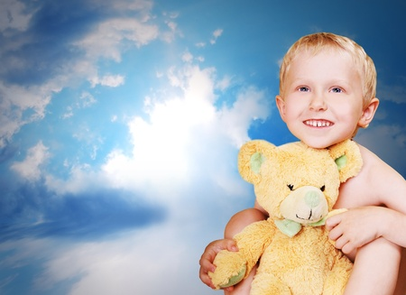 sunshine smiling pretty boy with tedde bear on dark blue sry Stock Photo - 9903853