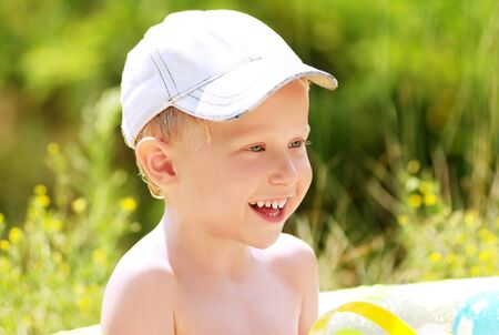 Happy smiling little boy on the green meadow Stock Photo - 10048953