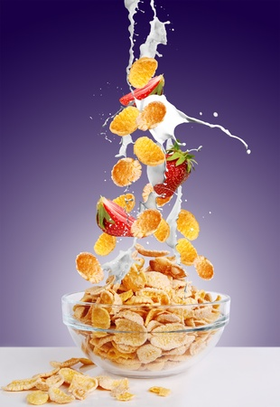 corn flakes: Gold corne flakes and the strawberry falls into the bowl with jets of milk on dark purple background