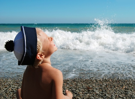 sailor hat: Little boy in sailor hat sits on the sea beach and smiling to sun