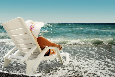 Young lady in hat sits in chaise lounge on the sea beach photo