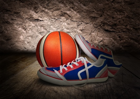 The pair of sport shoes and basketball ball on the wooden floor photo