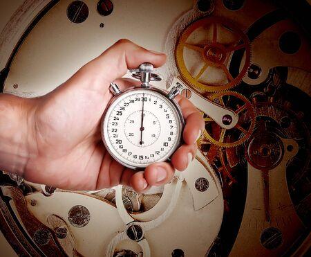 mans watch: Cron�metro en mano del hombre sobre un fondo oscuro de un mecanismo de reloj antiguo Foto de archivo