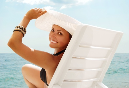 Portrait of smiling young woman in white hat at the sea view background photo