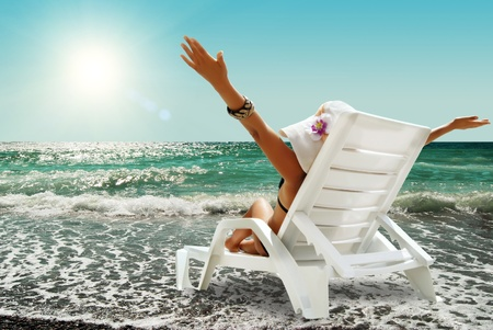 Gelukkige vrouw in chaise lounge op de zee strand in zonnige dag