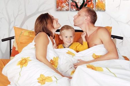 Young couple smiling family with little boy child play piddle in morning bed  Stock Photo - 10930497