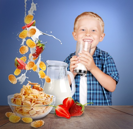 cornflakes: Image of smiling little boy with glass of milk and healthy meal on the wood table Stock Photo