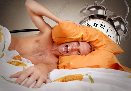 terribly: Terribly loud alarm clock at early morning for the sleeping man