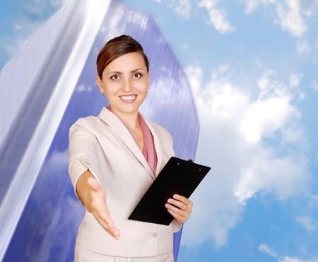 Genuinely smiling business woman with hand outstretched for a handshake on the business center and sky background photo