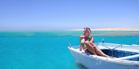 Young woman in old boat on the azure sea surface photo