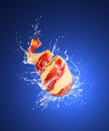 Red apple with the skin peeled like a spiral in water splashes on the dark blue background photo
