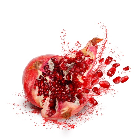 Falling down ripe pomegranate with cracks and splashes of juice and seeds on white background Stock Photo