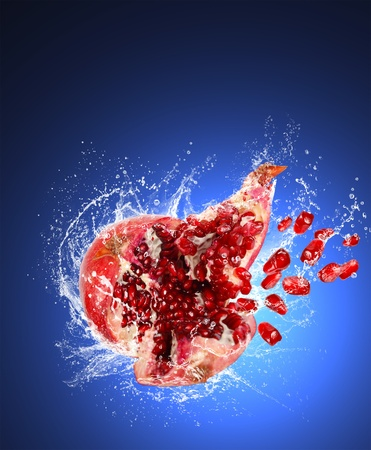 Cracked pomegranate with expanding grains in water spray and splashes on dark blue background photo