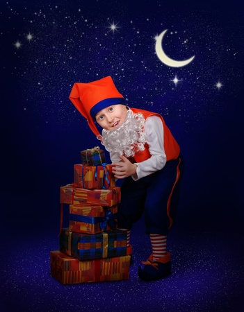 Funny little gnome with gift boxes at the magic christmas night photo
