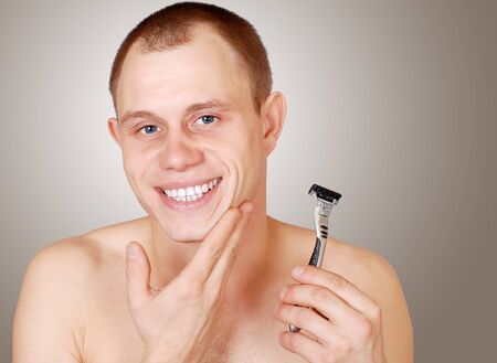 Smiling young man with a clean-shaven face and razor blades photo
