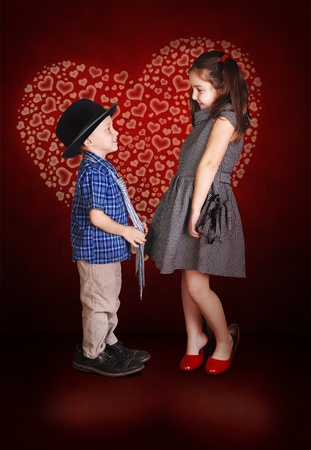 Young lady and little gentleman confession in love at the burgund background with shining  heart  photo