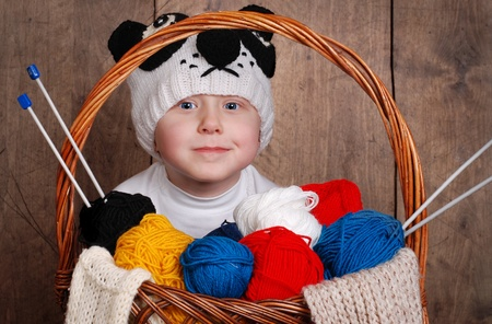 Little boy in knitting panda hat with wool yarn into basket photo