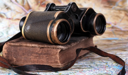 Binocular vendimia con el libro antiguo en el fondo del mapa topográfico
