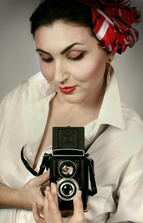 Beautiful young lady portrait with retro rhoto camera photo