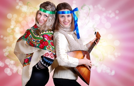 Two russian beauties with folk attributes on the pink background Stock Photo