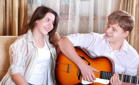 Two teenagers - boy and girl singing together by guitar at home photo