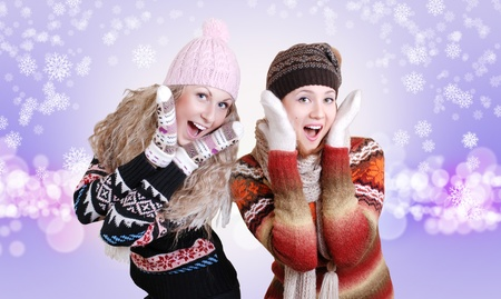 Two beautiful girls laughed in warm winter clothes over light purple background with snowflakes photo