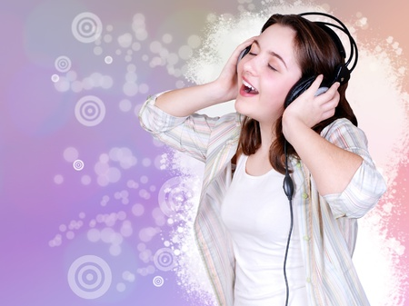 Teenage girl singing and listening music in headphones  on bright abstract background photo