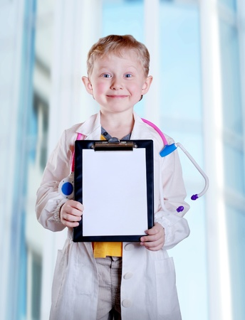 doctor toys: Cute little boy in doctor uniform with clip board in hands on light blue hospital background