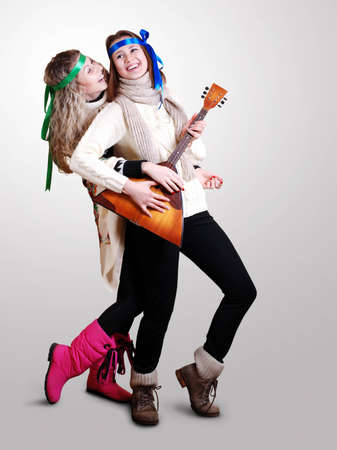 Two laughing beautiful girls dancing and plaing on balalaika.  photo