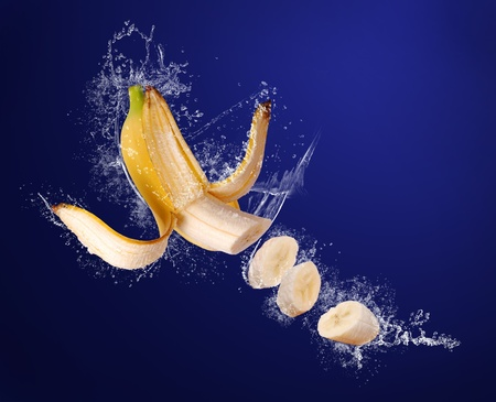 banana skin: Yellow banana with peeled  skin and sliced pieces  in water splashes on the dark blue background Stock Photo