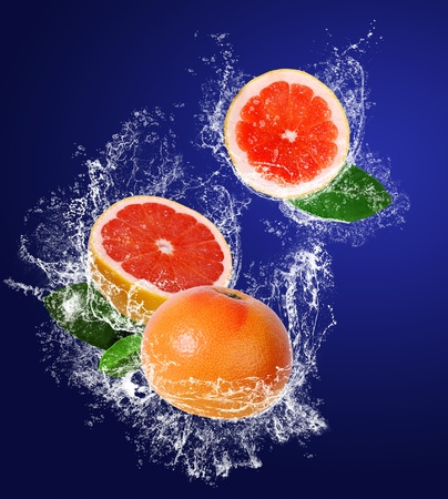 Red guicy grapefruits with leaves in water splahes on the dark blue background photo