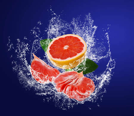 Red guicy segments of grapefruits with leaves in water splahes on the dark blue background photo