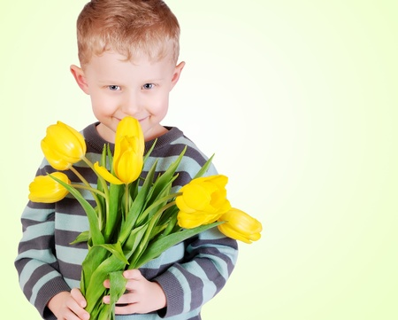 Cute little boy with bouqet of yellow tulips for gift Stock Photo - 12537625