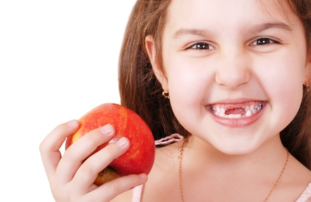 Portrait of Smiling pretty little girl without teeth with red apple in hand photo