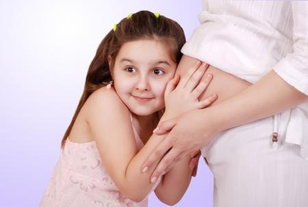 Little Daughter listen sirprisly near pregnant mom tummy photo