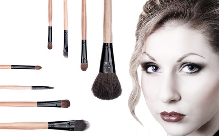 color skin brown: Portrait of beautiful blue-eyed girl with makeup brushes