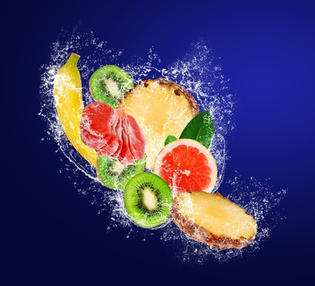 Sliced tropical fruit falling in water splahes on dark blue background photo