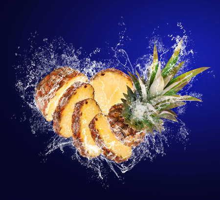 Slised Pineapple falling in water splashes on blue background photo