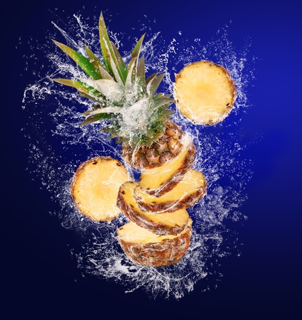 Slised Pineapple falling in abstract water drops on blue background photo