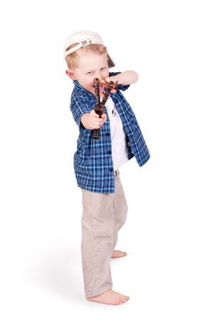 resentful: Expressive little boy bully shooting with slingshot over white background Stock Photo