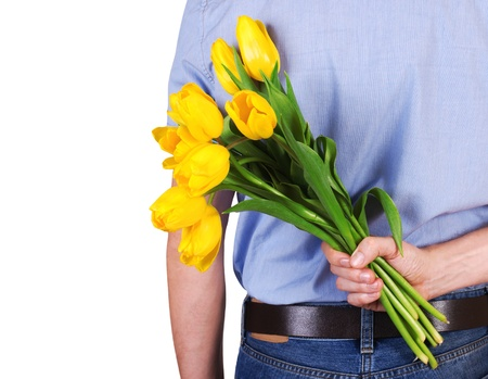 gift behind back: Closeup image of man back with bouquet of yellow tulips in hand