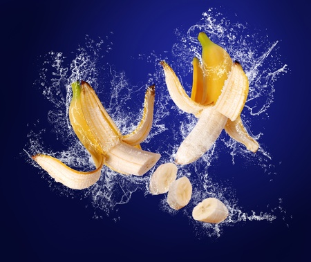 banana peel: Two Yellow bananas with the peeled  skin  in water splashes on the dark blue background