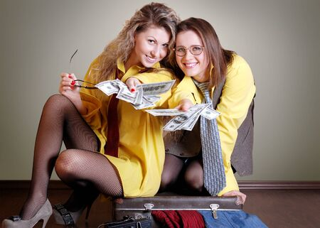Two beautiful girls in yellow man shirts with money and old suitcase photo