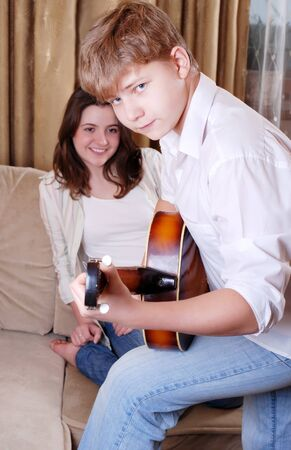 Teenage boy playing by guitar for his girlfriend at home photo