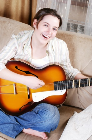 girl playing guitar: Happy teenage girl singing by guitar at home