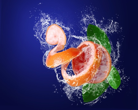 Red grapefruit with skin  peeled like a spiral and green leaves in water splashes on the dark blue background photo