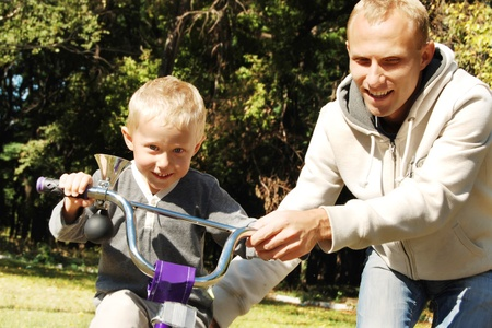Father help his little son to riding by bicycle photo