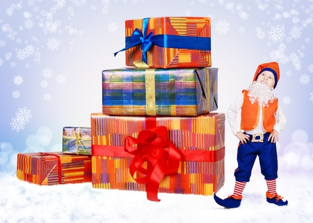 Little christmas elf standing near big gift boxes on the snow background photo